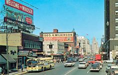 """Ouellette Avenue looking north towards Detroit near Park Street - early 1960s.    Old landmarks including Birks, George Wilkinson ad & a billboard welcoming U.S. travelers as they exited from the Detroit/Windsor tunnel.  """"I recall going downtown on the Erie bus for seven cents, hanging around in Smith's and the Metropolitan Store,"""" said local radio personality Wayne Stevens.  Saturdays at the Palace or Vanity to see a movie, a cartoon and then another movie – all for a quarter!"""