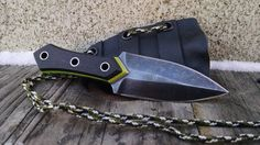 "Golden Minnow Neck Knife by RavenStag Design This little beauty is hand crafted from 01 tool steel heat treated, etched and stone washed finished to a high detail. The blade is 2""1/2 long, 5"" overall. The scales are made of Kydex , Lime Poly Micarta and Aluminum lining, with stainless steel pins . The holster is Kydex with 4 feet of paracord. Not a prop, a very sharp blade!"