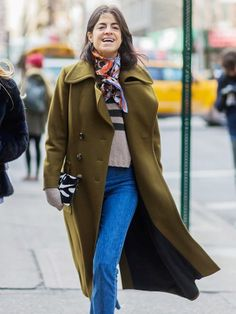 Leandra Medine wears a striped sweater, olive green coat, printed scarf, and jeans