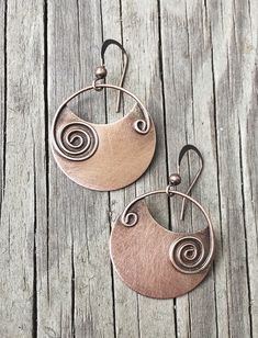 Copper earrings with copper spirals. I created these earrings by cutting copper discs and soldering on a hand-formed copper spiral made of square