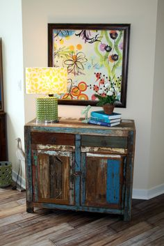 A funky fun vignette with happy artwork and a clever reclaimed wood cabinet - Eclectic Family Room. Designed by Bayberry Cottage who also serves South Haven, Kalamazoo, Saugatuck, St Joseph, & Holland.