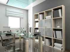 Modern home office in grey color design with glass topped-desk, modern desk chair and extensive bookshelves along one wall