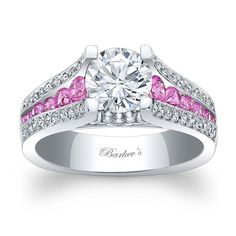 This sophisticated, vintage, white gold, three row diamond and pink sapphire engagement ring sports a round prong set diamond center. The shank features three rows, the center row is channel set with pink sapphires with flanking rows of pave set round diamonds. A milgrain finish adds the final touch of elegance to this classic ring.<br />  <br />  Also available in rose, yellow gold, 18k and Platinum.