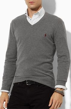 White dress shirt, grey sweater, and black pants with black belt and assorted bracelets.