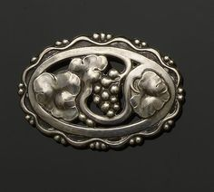 Georg Jensen: A brooch The shaped oval panel with pierced and embossed grape cluster and leaves, to fancy bead border, numbered 177, stamped 'Sterling' with maker's mark, length 5.8cm.