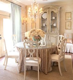 love the armoire, the chandelier, the chairs (especially the monogrammed ones on the wall), the framed artwork, the skirted table, the flowers. Not so much the curtains; they seem ... out of place?