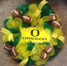 University of Oregon Ducks wreath in colors of yellow and green, accented with yellow and green ribbon as well as football ribbon. The center is a metal license plate.