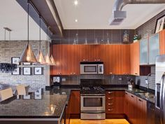 Appliances: Industrial Loft Style Kitchen. black kitchen appliances. black gas range. shiny gray countertop. wooden kitchen cabinet. stainless steel microvawe oven. transparent cone pendant light. stainless steel refrigerator. exposed brick kitchen.