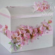 Свадебный сундучок, украшенный атласными лентами, декоративным яблоневым цветом и бусинами. Сундучок плотный, крышечка открывается. Внутри сундучок задрапирован тканью. Размеры: 23*16*21 смЦвет: розовыйВ интернет-магазине sovet-decor.ru Вы сможете подобрать множество великолепных свадебных аксессуа