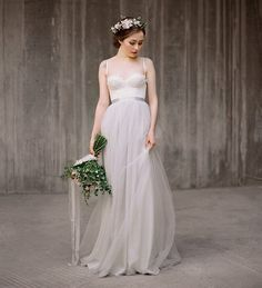 This gown features a beautiful fitted bodice with hand sewn corded lace appliqué, spaghetti straps and dreamy greyish tulle skirt. The skirt is
