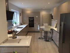 This galley kitchen incorporates a breakfast bar area to create a fantastic social area. With high gloss cashmere cabinets and Corian worktops. #German #Kitchen #HighGloss #Cashmere #Corian #DuPont #Neff