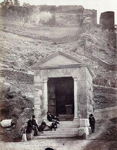 Templo junto al puente de Alcántara. Charles Clifford, 1859.  Alcantarinos luciendo sus mejores galas para la ocasión.  Obsérvese que el templo aún no tiene la puerta metálica que, por los datos que tenemos, fue colocada probablemente en este mismo año.