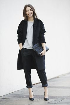 Shop this look on Lookastic: http://lookastic.com/women/looks/coat-crew-neck-sweater-clutch-chinos-pumps/4886 — Black Coat — Grey Crew-neck Sweater — Black Leather Clutch — Black Chinos — Black Leather Pumps