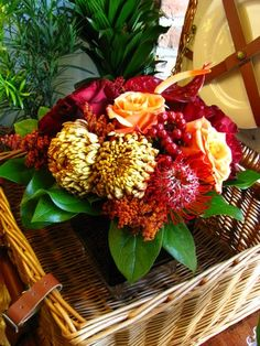 Autumn arrangement of red pin cushion protea, bronze mums, orange roses, red anthurium and hypericum berries. - Fly Me To The Moon Florists