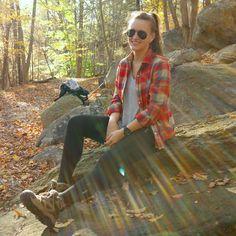 Fille assise sur une roche randonnée en montagne chemise à carreaux