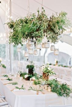 A lush chandelier made of thick green garlands with white roses, blue anemones and thistle accents | Brides.com