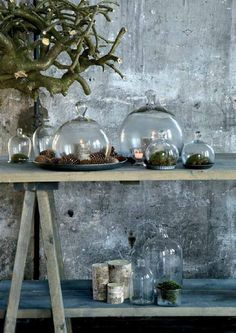 Decoration with pine cones, moss and candles under round glass domes via Woontrendz