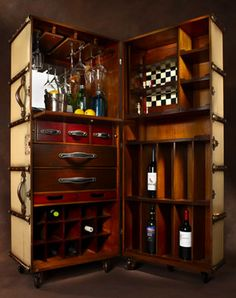 This bar is made in the style of turn-of-the-century travel trunks. Solid brass hardware and bridle leather accouterments complete a hand-built, two-part bar inside a large trunk set on sturdy wheel; home bar; #speakeasy party ideas, #trunk #bar