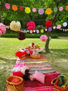 A pretty, picnic idea. Decorative pom pom garlands. Great, vibrant colours used in this picnic display.