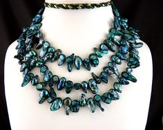 "This might be pushing it toward the Naturals because of the irregular natural material.  But the iridescence, the luxuriant nature of the color, and the ""heft"" provided by the multiple strands keeps this ""ornate"" and substantial enough, IMO.  Teal Striped Fireball Baroque Freshwater Pearl 54 Inch Hand Knotted Necklace. $59.00, via Etsy."