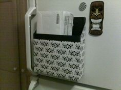 Cereal box covered in scrapbook paper with magnets on the fridge. For take out menus and pizza coupons