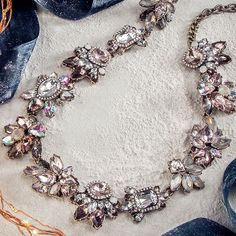 This statement necklace features iridescent floral motifs for a whimsical touch.