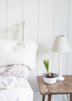 pink floral bedding against the white, tongue and groove panelling