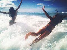 Girls in bikini on the seashore and swim in the sea