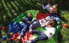 Anaokulu bahçe oyunları. Paraşüt, toplar ve çocuklar. Çimen, toprak ve güneş.