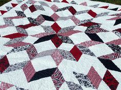 "This is a queen size quilt that I made for my brother Pierre and his wife Christa's wedding. It is 96 inches square. The fabric was cut using the GO! 6.5 inch hst die. Fabric is ""Black, White & Current"" by Color Principle for Henry Glass & Co. Also, the white and solid red, solid black are Kona solids by Robert Kaufman. This quilt was designed, machine pieced and quilted by me. Inspiration for this quilt came from maryquilts.com, Carpenter's quilt pattern."