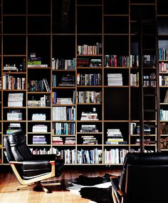 The huge bookcase, a focal point in the moody living area, contains design and art history books as well as historical tomes passed down through Merrick's family. The quietly sophisticated furniture and furnishings – vintage Tessa armchairs and an Ikea cowhide – work with rather than compete with the building's grand textural structure.