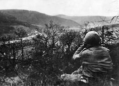An American soldier surveys the landscape of the Hürtgen Forest near the Roer River through a pair of binoculars. The height of Hill 400 gave its American defenders a panoramic view of the river and the surrounding countryside.
