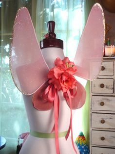Wouldn't these be a KICK on your summer-sundress mannequins? Wings;  3 wire hangers  2pr 3X pantyhose  duct tape  2 yds. elastic  needle and thread  scissors  two large silk flowers  ribbon  hot glue