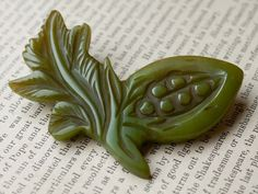"A beautiful green Bakelite ""peas in a pod"" brooch with brass closure."