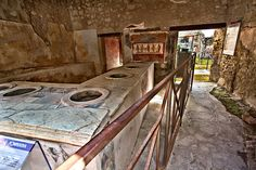 This taberna at Pompeii, considered a fast food joint of the ancient world, is one of many where Romans took their midday meal. Food was sco...