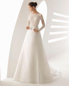 Klassisches Brautkleid aus strassbesetzter Spitze und Organza, lange Ärmel, V-Rückenausschnitt mit transparentem Einsatz. Kollektion 2018 Rosa Clará.