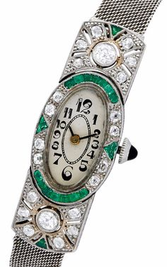 Art Deco Emerald, Diamond and White Gold Wristwatch, circa 1930  The diamond-set case accented by calibre-cut emeralds, centering an oval grey dial with Arabic numerals, sapphire crown, quartz movement, in 18k white gold, and joined to an adjustable 14k white gold mesh strap