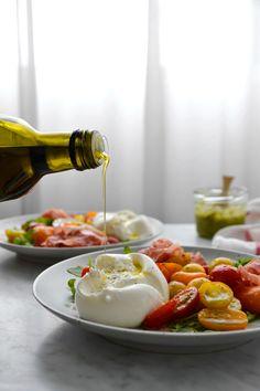 400g de tomates cerises multicolores coupées en deux     2 c. à s. de pesto     3 c. à s. d'huile d'olive     2 belles poignées de roquette     2 boules de burratina ou de mozarella     4 tranches de jambon cru     sel et poivre du moulin       2 c. à s. de pesto     3 c. à s. d'huile d'olive     2 belles poignées de roquette     2 boules de burratina ou de mozarella     4 tranches de jambon cru     sel et poivre du moulin