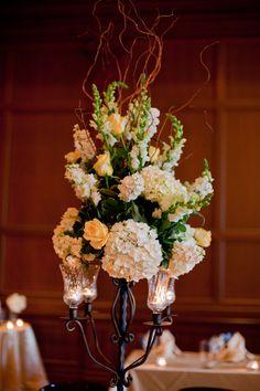Iron candelabra with sherbert orange roses, white hydrangea, and white snapdragons   villasiena.cc