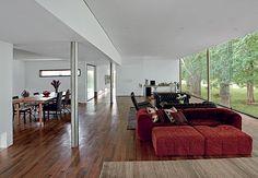 Os pilares de aço cilíndrico de 25 cm permitiram criar os vãos livres de 7,30 x 5,50 m. Aqui ficam as salas de estar e jantar e o escritório. O espaço tem assoalho de ipê. Projeto do arquiteto Marco Peres