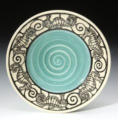 Sgraffito work from my new favorite ceramics studio. I love that the artist chose to leave a distinct spiral from working the plate by hand, and it shows nicely through the glaze. Also the separation of the solid blue and the carved region makes this piece feel clean and well-composed.   ©BassRiverPottery