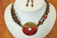 Beautiful Unakite Jasper focal piece in shades of red, salmon & moss green flanked my strands of carnelian, unakite & copper metal & glass beads. Matching earrings. www.facebook.com/lunaleafstudio