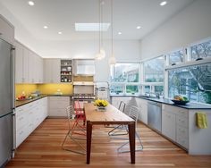 The kitchen addition connects with the rear green space and floods the room with natural light through large horizontally banded, counter height windows.