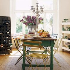 second hand table with wonderful jade green legs and yellow metal chairs. the wine holder is simply a board with holes cut in. Love it!