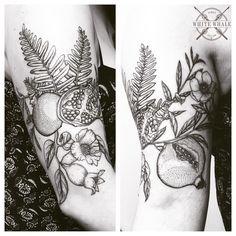 half sleeve tattoo of blossoms, pomegranates, and ferns