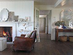 dark floors, white walls, worn leather chair...rustic white interior