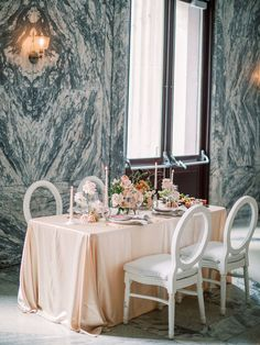 A federal courthouse turned boutique hotel played host to this fine art elopement with a vintage inspired tulle wedding dress, a dogwood flower bouquet and a peach and persimmon tablescape with speckled abstract candle holders. If you love classic, luxe wedding ideas, you will not be disappointed by these magical elopement scenes! #courthousewedding #elopementideas #cutecouple