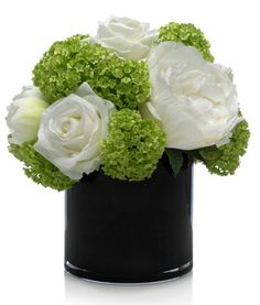 bright green snowball and white peonies spill over a black glass vase and a lush magnolia blossom is showcased in a silver ceramic cube with cross hatch motif.