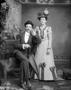 Studio portrait of a man posed sitting on the arm of a chair and holding an umbrella, and a woman posed standing, possibly Mr. and Mrs. Olaf Olson (c. 1898).