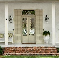 Breezy Neutral Shutters | Four sets of French doors, each flanked with 10-foot louvered shutters, stand in for front windows and blur the line between indoors and out. | SouthernLiving.com